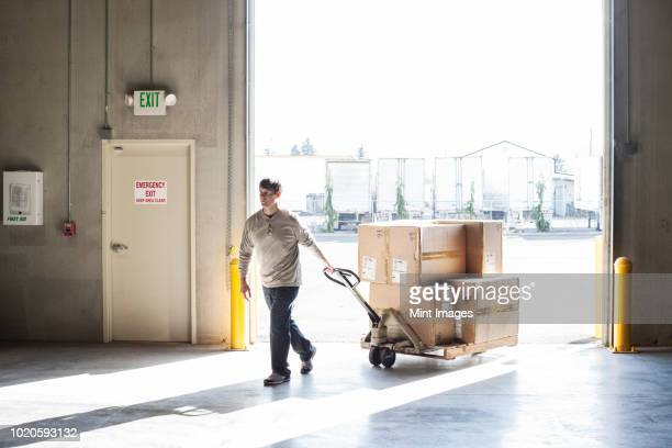 A male warehouse worker moving boxes of products using a manual pallet jack.