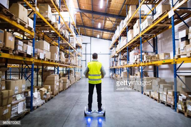 male warehouse worker on hoverboard. - hoverboard stockfoto's en -beelden