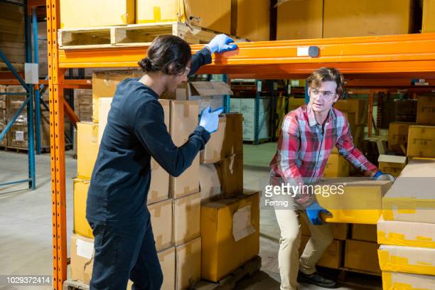 a male warehouse worker removing a box from under some racking as a supervisor instructs him on proper technique - ergonomics stock photos and pictures