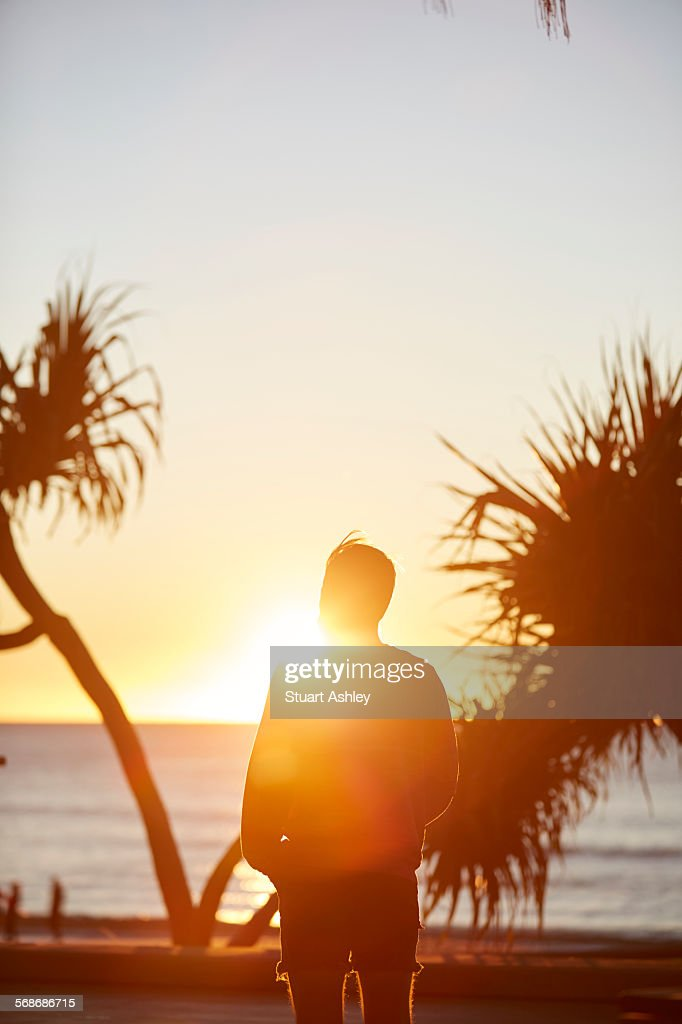 Male watches over sunrise ocean : Stock Photo