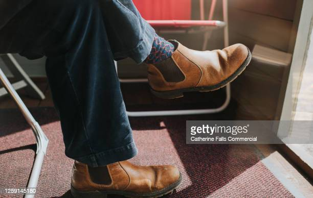 male wearing brown leather chelsea boots, legs crossed at the knee, sitting in a sun room. - tranquil scene stock pictures, royalty-free photos & images
