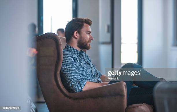 Male web designer sitting on armchair in office