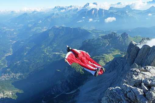 Male wingsuit BASE jumper taking off from cliff edge - gettyimageskorea