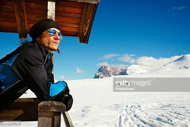 male winter sports athlete pausing in scenic alps landscape
