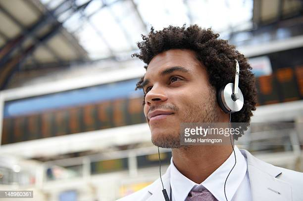 male with headphones at train station - listening stock pictures, royalty-free photos & images
