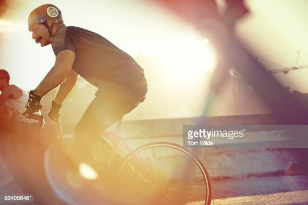 Male with large moustache cycles with sun flare