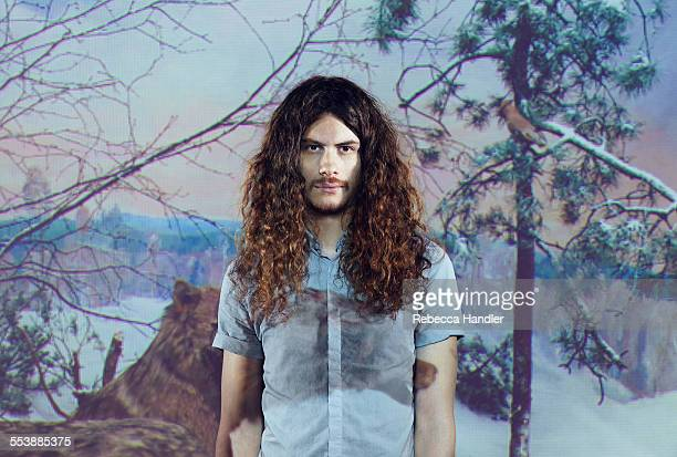 Male with long curly hair in scenic background