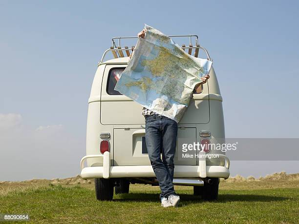 Male with map outside camper van