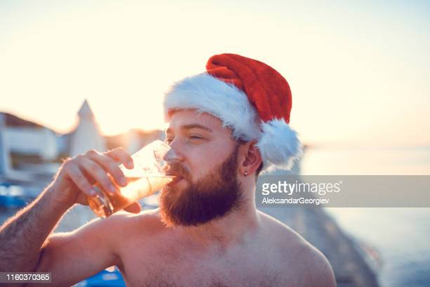Male With Santa Hat Drinking Juice At The Beach