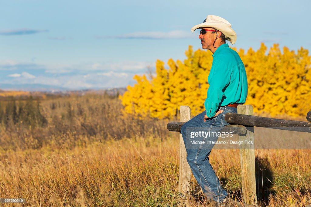 Male with straw cowboy hat and sunglasses sitting on top of a wooden fence  looking into 9f99301db208