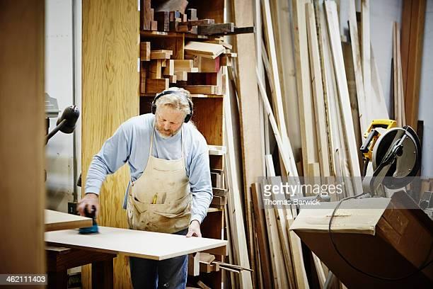 Male woodworker in woodshop sanding cabinet panel