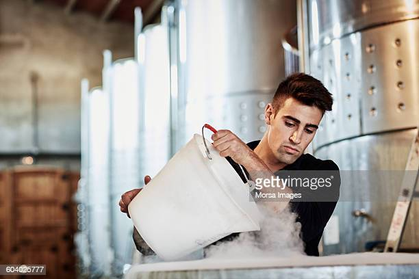 Male worker adding dry ice in wine