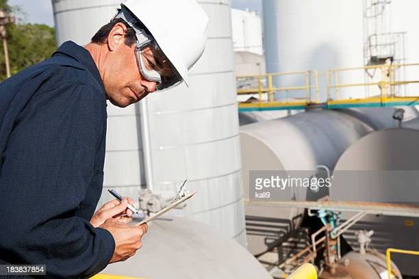 male worker at industrial plant writing on clipboard - storage tank stock photos and pictures