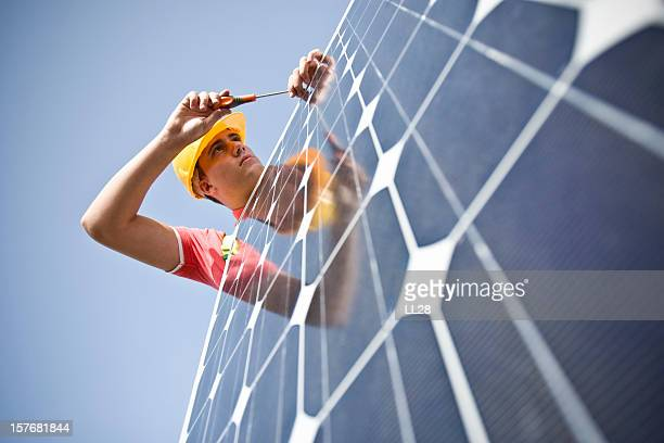 male worker at work fixing solar panel - solar panels stock photos and pictures