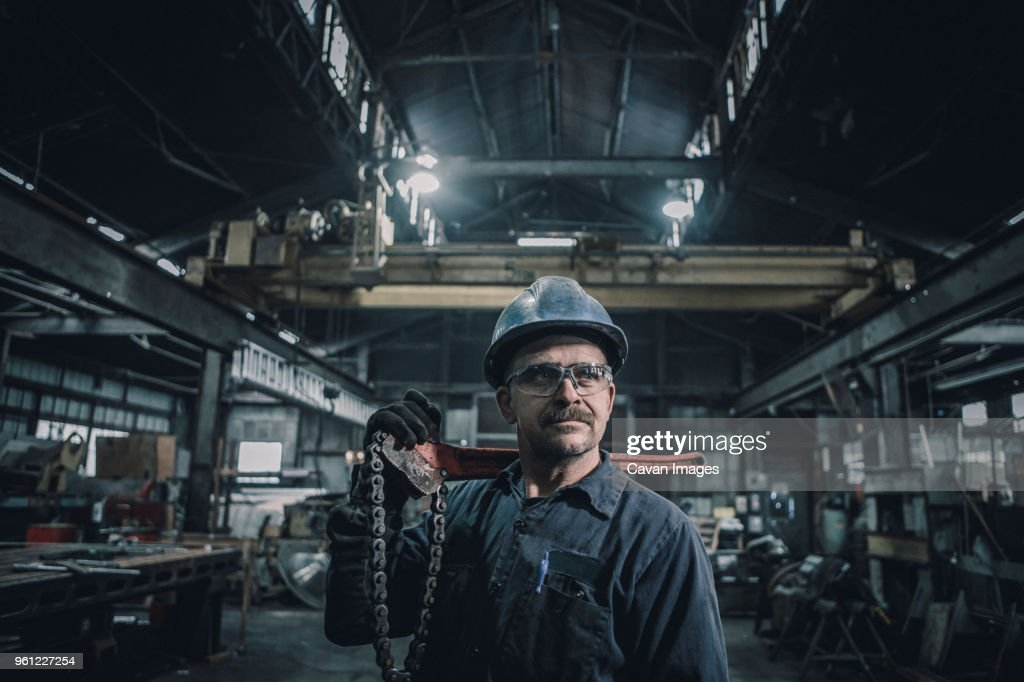 Male worker carrying work tool looking away while standing in factory : Stock-Foto