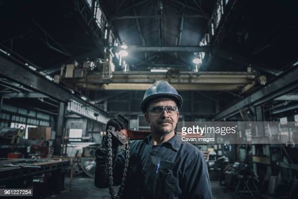 Male worker carrying work tool looking away while standing in factory