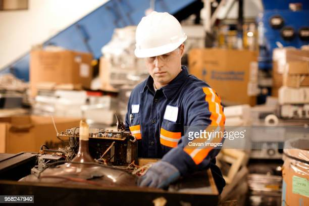 Male worker checking electrical equipment in recycling plant