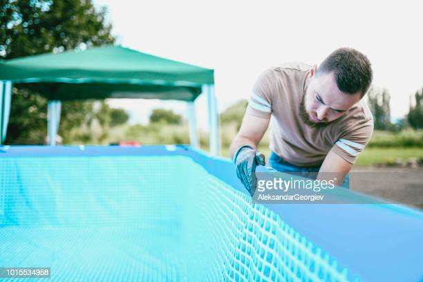 Male Worker Checking If The Pool Is Properly Balanced