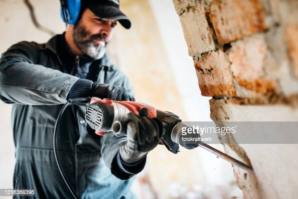 male worker demolishing wall with drill at house - demolishing stock pictures, royalty-free photos & images