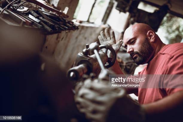 Male Worker Fixing Machine In Workshop