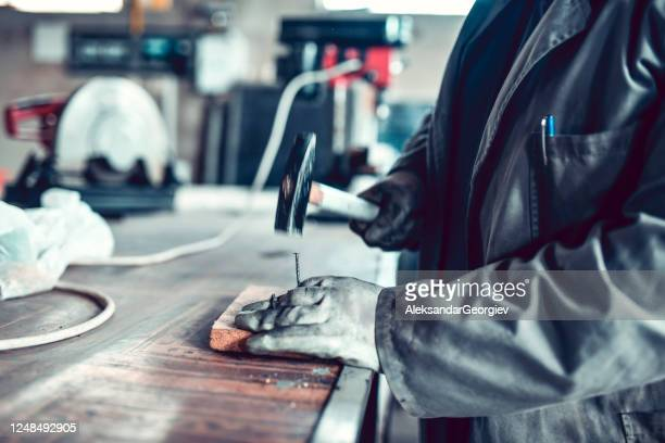male worker hammering nail into a piece of wood - strike industrial action stock pictures, royalty-free photos & images