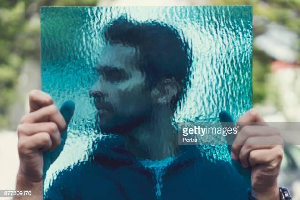 Manliga arbetare håller blå frostat glas utomhus