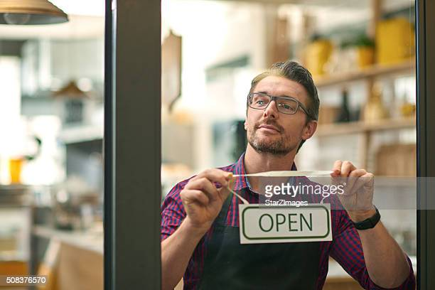 Male worker holding open sign through glass of cafe door