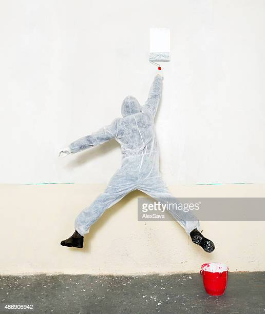 Male worker in a painting suit painting a white wall