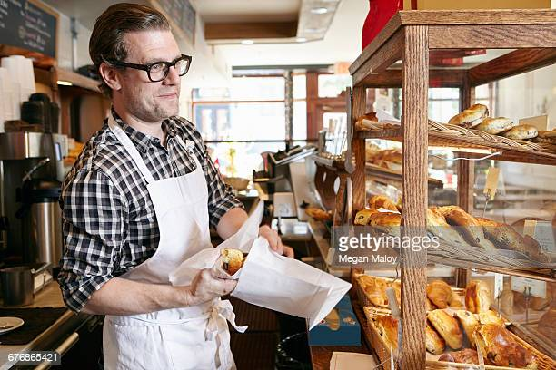 Male worker in bakery, putting baked goods into paper bag for customer