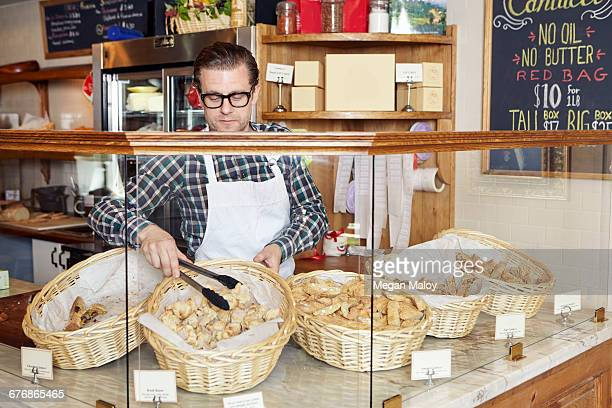 Male worker in bakery, taking fresh goods from basket