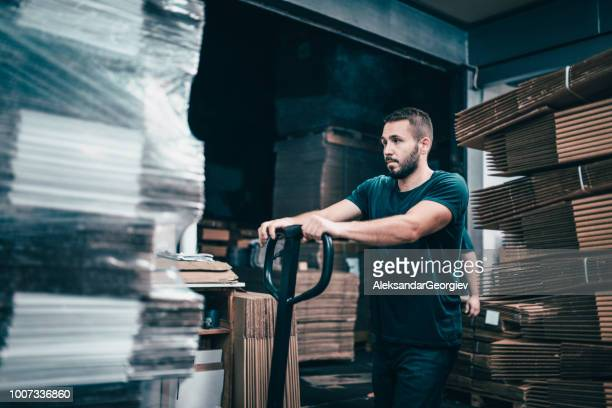 male worker in cardboard factory pushing pallets on to transportation cart - working overtime stock pictures, royalty-free photos & images