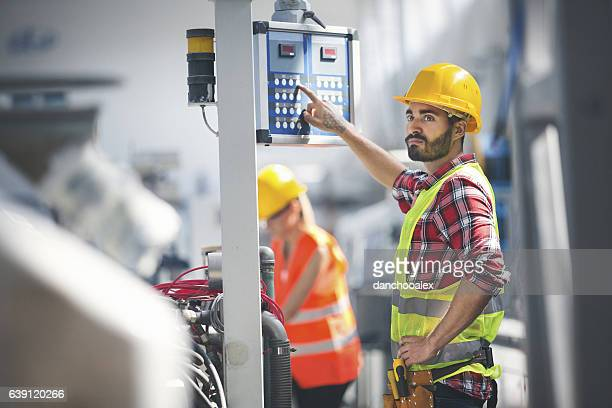 Male worker in factory using control panel