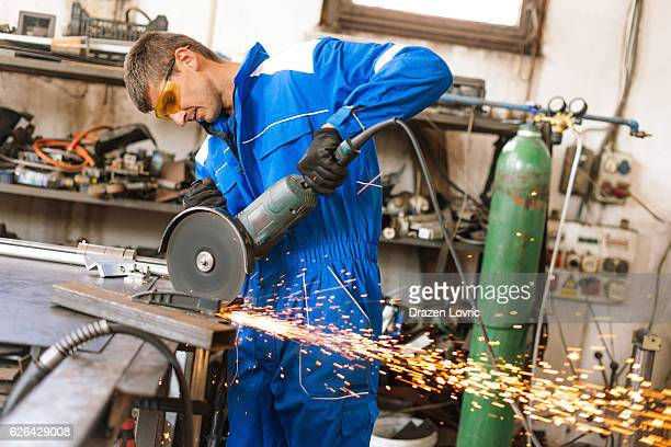 Male worker in factory using grinder