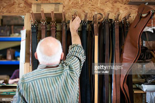 Male worker in leather workshop, hanging leather belts on rack, rear view