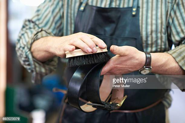 male worker in leather workshop, polishing belt, mid section - leather belt stock pictures, royalty-free photos & images