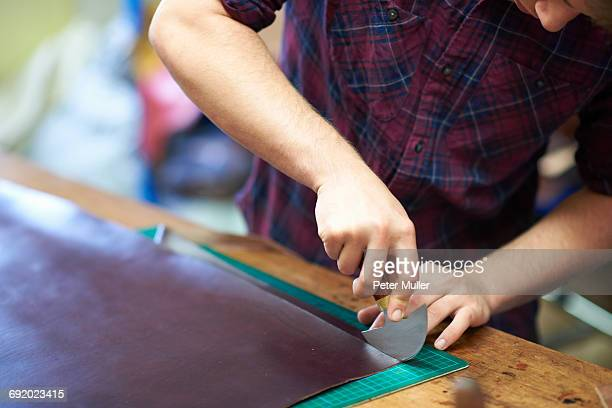 male worker in leather workshop, using cutting tool to cut leather, mid section - leather shirt stock pictures, royalty-free photos & images