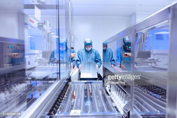 male worker inspecting flex circuit in flexible electronics factory clean room - place of research stock pictures, royalty-free photos & images