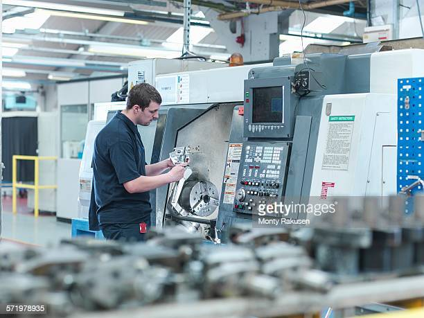 Male worker inspecting parts on CNC lathe in engineering factory