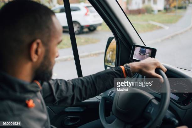 Male worker looking at device screen while driving delivery van in city