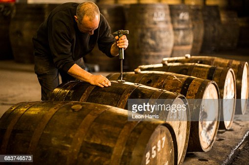 Male worker opening wooden whisky cask in whisky distillery
