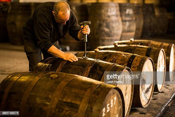 male worker opening wooden whisky cask in whisky distillery - scotland imagens e fotografias de stock