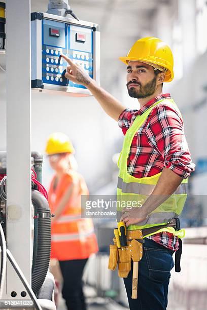 Männliche Arbeiter Betrieb einer Maschine in Fabrik
