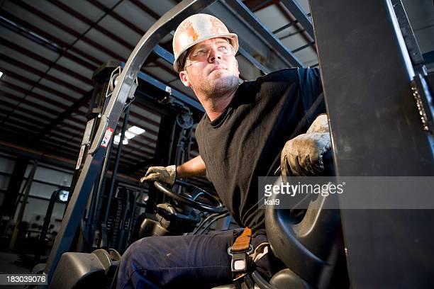 Hombre trabajador funcionamiento de carretilla elevadora en almacén