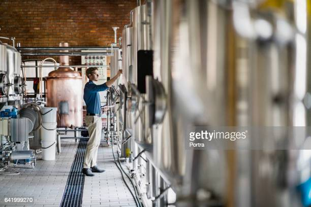 Male worker operating machinery in brewery