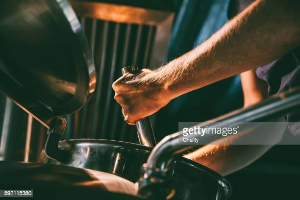 male worker operating machinery in brewery - storage tank stock photos and pictures