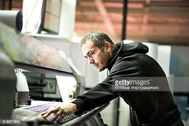 male worker operating on industrial printer - printout stock pictures, royalty-free photos & images