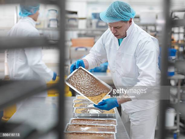 male worker pouring chocolate in cake factory - chocolate factory stock photos and pictures