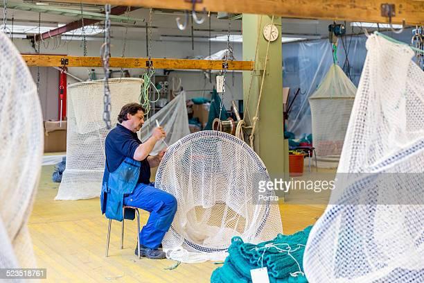 Male worker preparing net in fishing industry