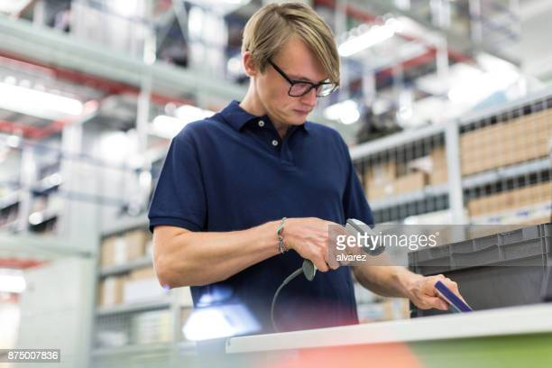 Male worker scanning package for delivery