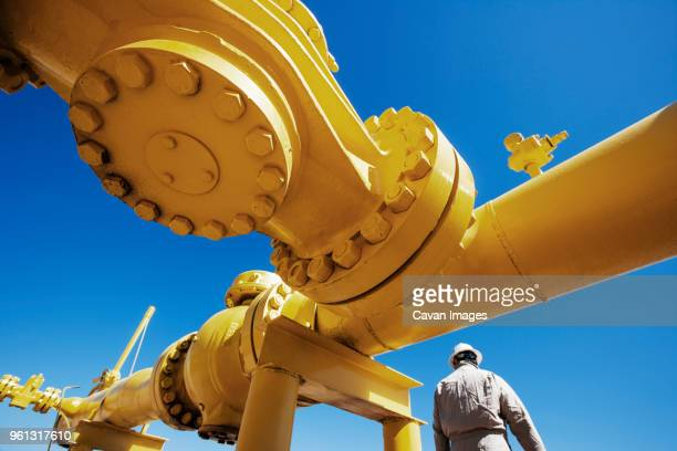 male worker standing below yellow painted pipeline at oil refinery - oil industry stock pictures, royalty-free photos & images